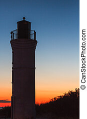 Robert H. Manning Memorial Lighthouse silhouetted by the sunset sky over Lake Michigan