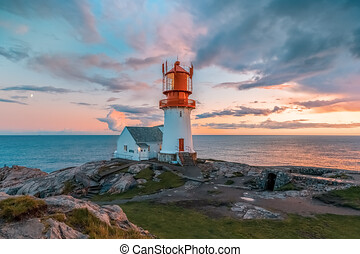 lighthouse surrounded by rocks at sunset, lighthouse surrounded by rocks near the ocean