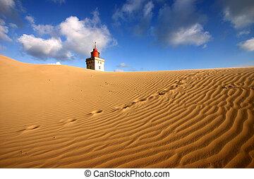lighthouse under sand in Denmark. The wind has blown sand...