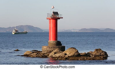lighthouse with fishing boat against blue sky