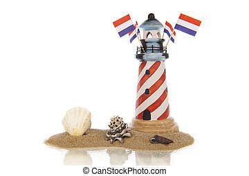 Lighthouse with flags and assorted shells in sand