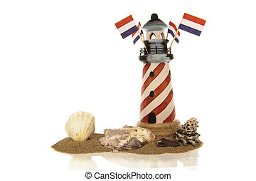 Lighthouse with flags and shells in sand