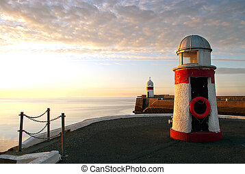 Lighthouses on breakwater wall with calm sea during sunrise....