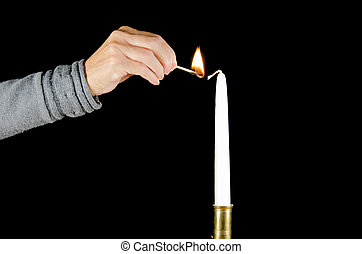 Lighting a candle - A hand with a match is lighting a white...