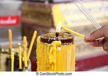 Lighting a candle in a temple