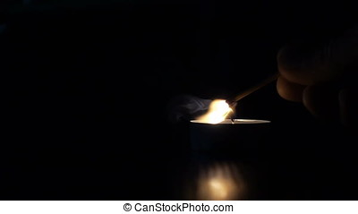 Lighting a match stick from candle, slow motion