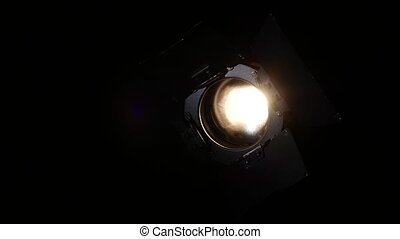 Lighting equipment, flash or spotlight, with shadow on black background, close up
