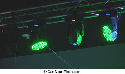 Lighting equipment rotating spotlights under the ceiling above the stage
