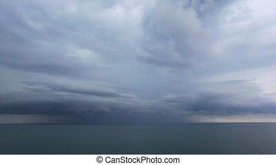 lighting from dark storm clouds above waving Black Sea