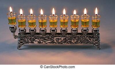 Lighting oil candles in menorah for Hanukkah