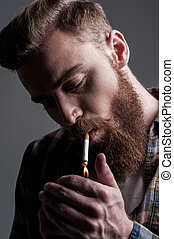 Lighting up cigarette. Handsome young bearded man lighting up a cigarette while standing against grey background