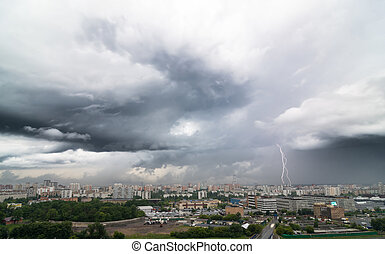 Lightning bolt over city in stormy day.