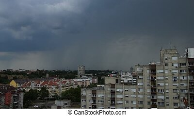 Stormy clouds and tree lightnings during daytime above city residential area