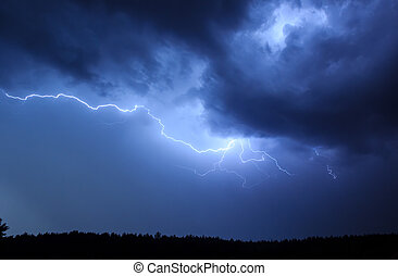 Lightning in sky on the background of trees