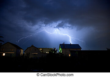 Lightning in the cloudy sky over village