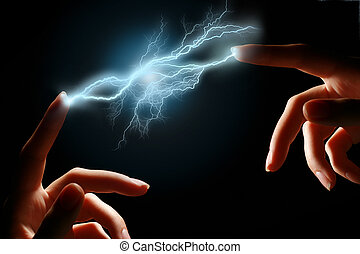 Lightning. - Hands and electric discharge over black...