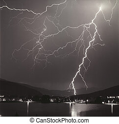 A night time electrical storm directly over Vail Valley Colorado with the city lights and reflections in the lake.