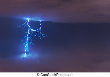 Lightning strike flash, electric discharge between clouds at night.