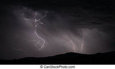 Lightning strike over mountain range with clouds - Closeup...