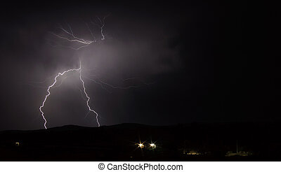 Lightning strike over mountain range with clouds - Long shot...