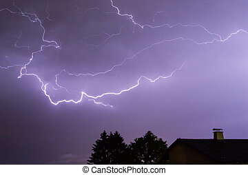 Lightnings over a house and a tree