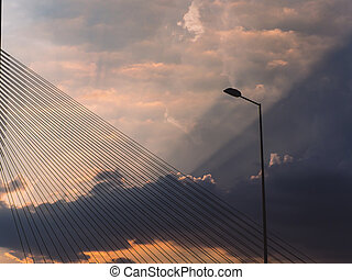 Lightpost and suspension bridge cables with sunbeams bursting through the clouds