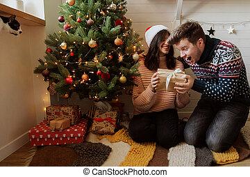 lights., ögonblick, nymodig, jul gåvor, under, holdingen, familj, gåva, träd, room., lycklig, spänd, festlig, utbyte, par, överraskning, munter, ung