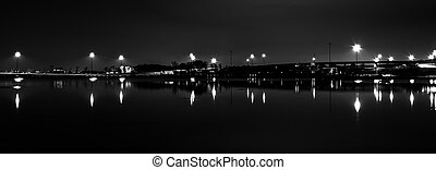 Lights and highways reflecting in the Potomac River at night, seen from National Harbor, Maryland.
