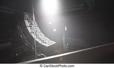 Multiple black confetti lights hanging on the ceiling of a concert stage with other wires in an empty auditorium with facing towards the stage