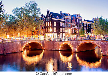 Lights of Amsterdam - Amsterdam canal bridges illuminated at...