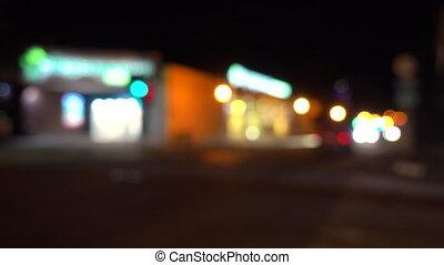 Lights of night city. Passing cars, road, restaurants.