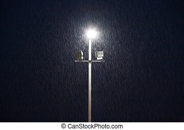 lights on a sports field at evening in the rain