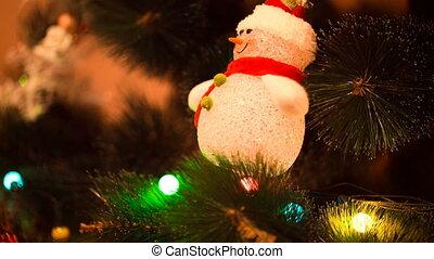 lights snowman hanging on Christmas tree
