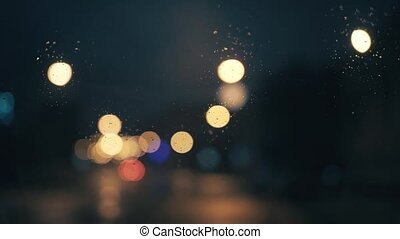 Lights the night city through the glass of the car. There is light rain
