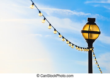 Lights Under the Sky - Yellow illuminated awry lamppost and ...