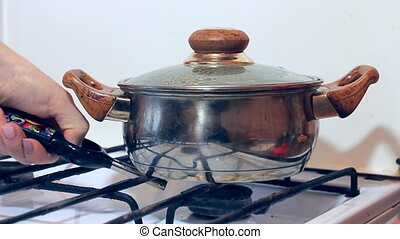 Lights up gas under a saucepan on a gas stove - The hostess...