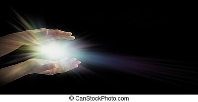 Pair of female hands emerging from the darkness with an explosion of white and rainbow tinted light energy between parallel hands