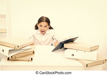 Like a fury. Angry pupil clenched her hands into fists. Little girl dont like reading lesson book in school. Small child refuses having literature lesson. Schoolgirl hates reading school book at desk