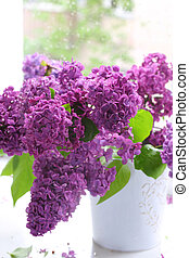 Lilac bouquet in a vase against a window