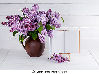 Lilac Bouquet in clay jug with open book with place for your text or picture on background of white wooden planks