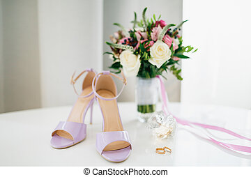 Lilac bride's sandals on the table with the bride and groom's wedding rings and a bouquet of flowers in a vase.