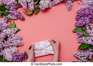 Lilac flower blossoming spring and hands with a gift on a pink background