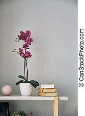 lilac flower is in a pot on the shelf. Interior detail.
