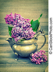 Lilac flowers in antique vase on wooden background. Vintage style toned picture