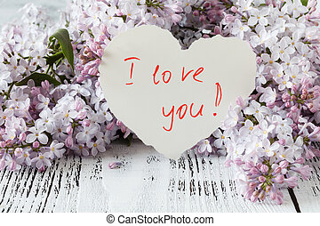 Lilac flowers on a old wooden background and heart with note i love you