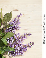 Lilac flowers on a wooden surface.