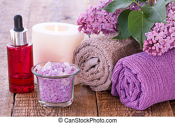Lilac flowers, red bottle with aromatic oil, burning candle, bowl with sea salt and towels on wooden boards.