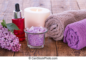 Lilac flowers, red bottle with aromatic oil, burning candle, sea salt and towels