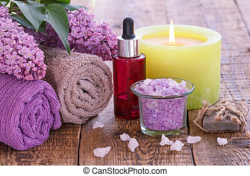 Lilac flowers, towels, red bottle with aromatic oil, burning candle, bowl with sea salt and soap.