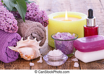Lilac flowers, towels, red bottle with aromatic oil, burning candle, bowls with sea salt and soap.